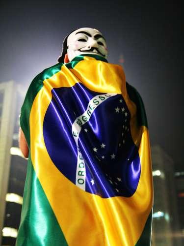 18 de junho - Com máscara e bandeira brasileira envolta no corpo, manifestante participa de protesto em São Paulo