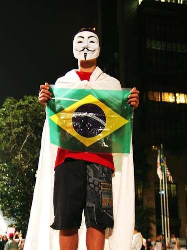 18 de junho - Com máscara símbolo dos protestos, manifestante posa com a bandeira brasileira