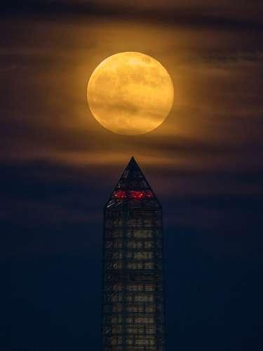 24 de junho - A Superlua é vista sobre o Monumento a Washington no domingo, dia 23, na capital dos Estados Unidos. Neste ano, a Superlua é até 13,5% maior e 30% mais brilhante que a típica Lua Cheia. Esse fenômeno é o resultado do satélite natural da Terra atingindo o perigeu  quando fica à menor distância em relação ao planeta