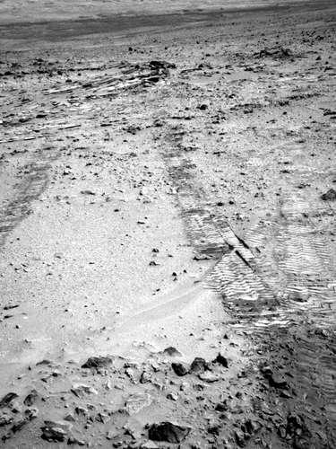 O robô Curiosity registrou os próprios rastros deixados durante seu trajeto no solo de Marte. As marcas anteriores (direita) correspondem à passagem peloCuriosity há sete meses pela área de Glenelg, próximo ao local onde houve o pouso. O nome da região é um palíndromo (palavra que mantém o mesmo nome quando lidade trás para frente): algo considerado adequado quando o local foi batizado, já que o robô passaria por ali na ida e na volta