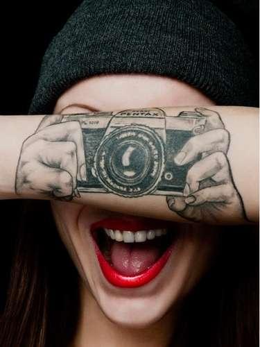 A tatuagem de máquina fotográfica Pentax no braço criou um efeito trompe l'oeil