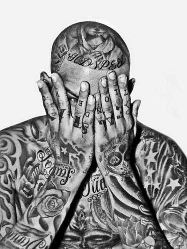 Homem mostra corpo coberto por tatuagens, com desenhos que chegam a simular seus cabelos. No topo da cabeça, um ser com capa