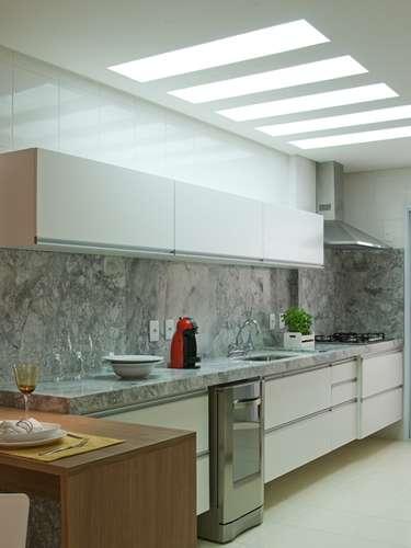 A cozinha apresenta móveis brancos e pia e parede cinza. A proposta é da arquiteta Lucilene Leitte. Informações: (11) 2534-4710