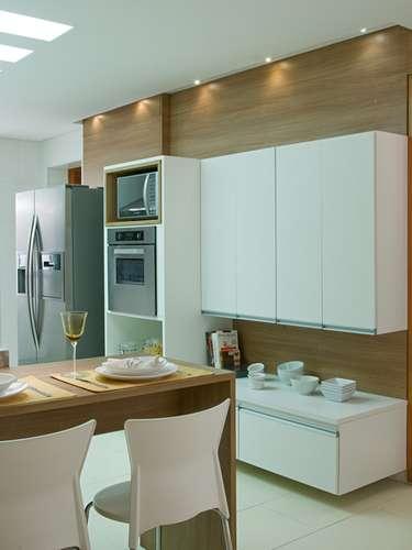 Os móveis brancos ficam em um painel em tom de madeira e oferecem nichos para forno e micro-ondas, no projeto da arquiteta Lucilene Leitte