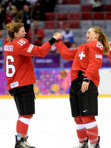 As meninas do time da Suíça do hóquei sobre o gelo mostram os cabelos após tirarem o capacete
