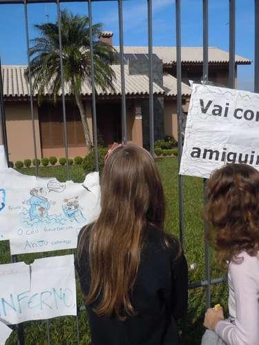 Através da grade e dos cartazes, amigas olham a casa onde Bernardo vivia