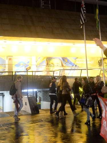 24 de maio - Fachada de um banco, com brasileiros torcendo pela Copa, contrastam com cenário de protesto nas ruas