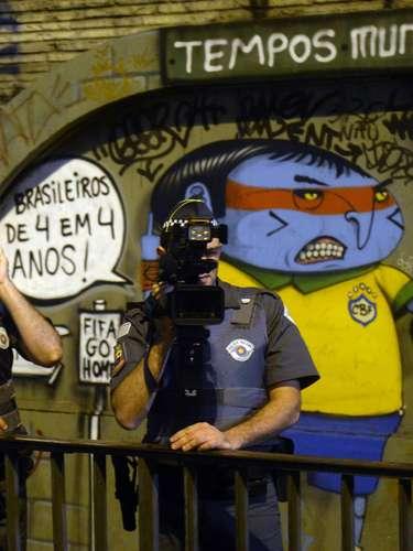 24 de maio - Policiais se posicionam em frente a um grafite, durante protesto em São Paulo