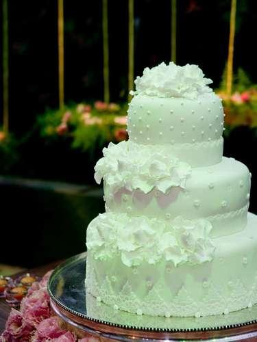 Bolo redondo branco de três andares coberto com pasta americana com detalhes de flores e renda, Simone Amaral - Sugar and Arts.Preço:R$ 200 o quilo de andar verdadeiro, andares falsos e flores são cobrados a parte
