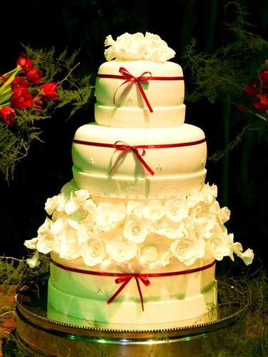 Bolo redondo branco de três andares coberto com pasta americana com detalhes de flores e fitas, Simone Amaral - Sugar and Arts.Preço:R$ 200 o quilo de andar verdadeiro, andares falsos e flores são cobrados a parte