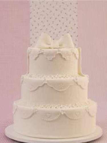 Bolo redondo de três andares branco coberto de pasta americana com fita e renda, Special Cake.Preço:a partir de R$ 100 o quilo