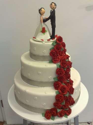 Bolo redondo de três andares branco coberto de pasta americana e decorado com cascata de rosas vermelhas, Wayne Ferreira. Preço: R$ 120 o quilo