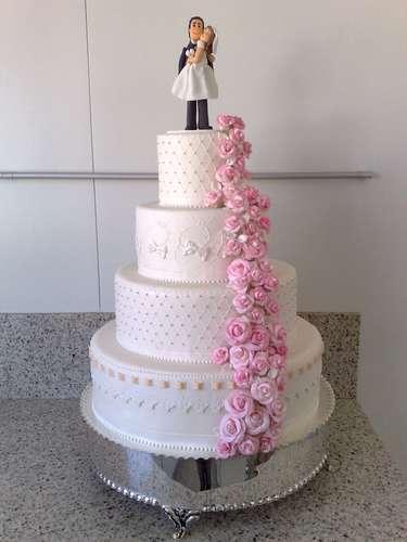 Bolo redondo de quatro andares branco coberto de pasta americana e decorado com cascata de rosas, na lateral de cada andar um tipo de bordado diferente, Wayne Ferreira.Preço:R$ 140 o quilo