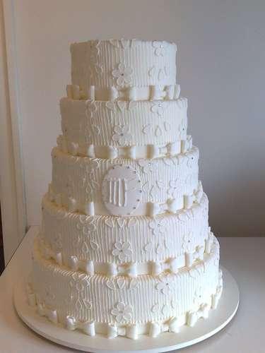 Bolo redondo de cinco andares branco coberto de pasta americana e decorado com trabalho imitando renda em glacê, Wayne Ferreira.Preço:R$ 130 o quilo