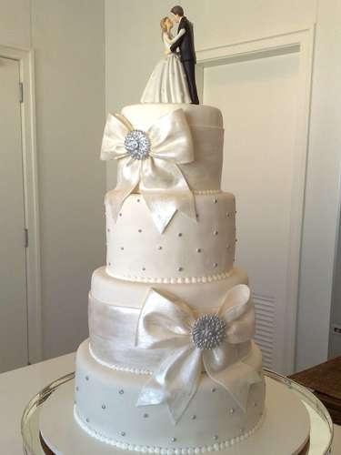 Bolo redondo de quatro andares branco coberto de pasta americana e decorado com laços, Wayne Ferreira.Preço:R$ 110 o quilo