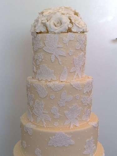 Bolo redondo de quatro andares amarelo coberto de pasta americana e decorado com flores brancas e alto relevo, Wayne Ferreira.Preço:R$ 120 o quilo