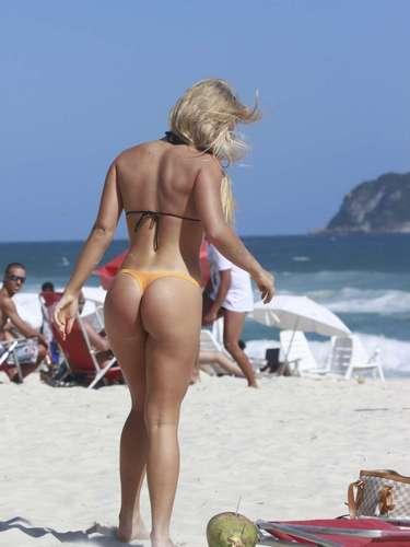 Janeiro 2013 -Thaiz Schmitt mostrou a boa forma ao usar um biquíni laranja e preto para curtir a praia da Barra da Tijuca, no Rio de Janeiro, na última quarta-feira (23). A modelo, que é coelhinha da 'Playboy', se bronzeou, se banhou no mar e escutou músicas em seu iPod