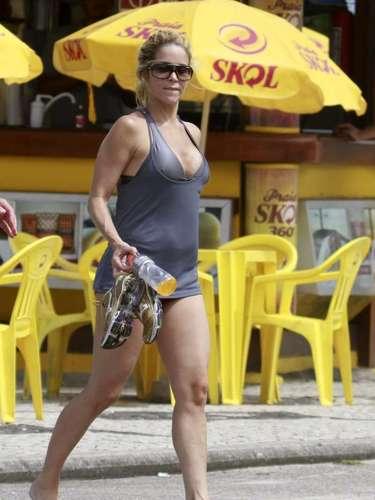 Abril 2013 -Danielle Winits aproveitou o calor no Rio de Janeiro para ir à praia da Barra da Tijuca, nesta quinta-feira (4). A atriz estava com o namorado, o jogador de futebol Amaury Nunes. O casal parece ter se exercitado, já que Winits apareceu segurando um par de tênis