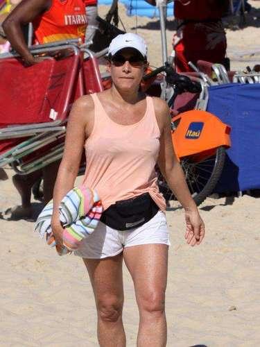 Junho 2013 - Totia Meirelles aproveitou o domingo (2) ensolarado para curtir a praia do Leblon ao lado do marido, o médico Jaime Rabacov, a enteada Olívia e seus filhos