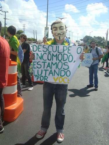 Manifestante exibe cartaz sobre os protestos no País