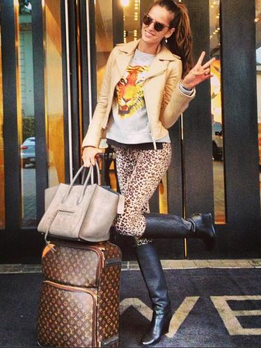 Izabel Goulart divulga look usado em viagem para Santiago, no Chile, com calça de oncinha, moletom com estampa de bicho, jaqueta de couro e botas de canos longos