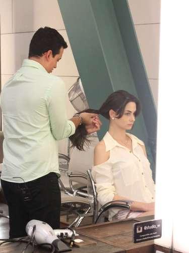 Primeiro, coloque todo o cabelo para a lateral do rosto, caindo sobre um dos ombros. Em seguida, prenda todos os fios em um rabo de cavalo e coloque o elástico na altura das orelhas