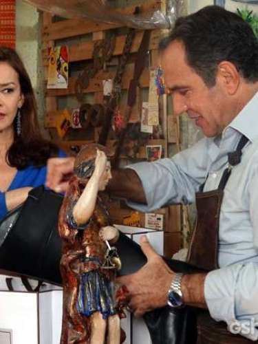Virgílio mente para Helena dizendo que encontrou um cliente que havia desmarcado a visita. A leiloeira fica desconfiada