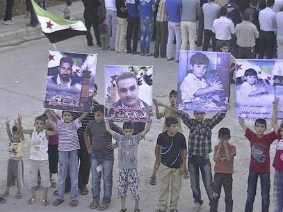 Boys hold posters of people whom protesters say were killed by forces loyal to Syria's President Bashar al-Assad, during a demonstration in Deraa June 17, 2012. Picture taken June 17, 2012. Foto: Handout / Reuters In English