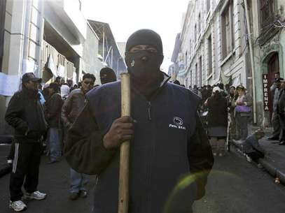 A police officer in civilian clothing takes part in a riot in La Paz June 24, 2012. Some members of the police and their wives occupied police barracks and marched in their fourth day of protests against low wages according to local media. Foto: David Mercado / Reuters In English