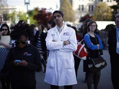 Doctor Vivek Murthy stands among other bystanders during the first day of legal arguments over the Affordable Care Act outside the Supreme Court in Washington March 26, 2012. Foto: Jason Reed / Reuters In English