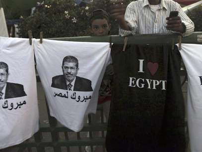"A boy stands near t-shirts with images of elected president Mohamed Mursi and words that read ""Congratulations to Egypt"" that are sold during a sit-in against the military council and the decision to dissolve parliament, at Tahrir Square in Cairo June 28, 2012. Foto: Amr Abdallah Dalsh / Reuters In English"