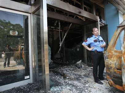 A security guard stands near a damaged van outside the burnt entrance of Microsoft's Greek headquarters following an attack at Marousi suburb, north of Athens June 27, 2012. Foto: John Kolesidis / Reuters In English