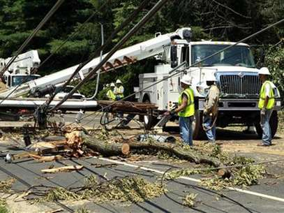Utility workers try to free up power lines after a huge tree fell across major road in Falls Church, Virginia July 2, 2012. Foto: Kevin Lamarque / Reuters In English