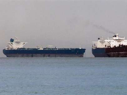 "Vessels sail past Malta-flagged Iranian crude oil supertanker ""Delvar"" (L) anchoring off Singapore March 1, 2012. Foto: Tim Chong / Reuters In English"