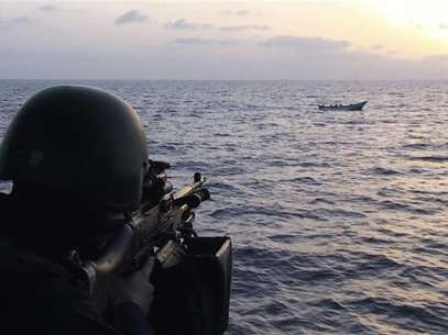 A soldier aboard the Swedish corvette HMS Malmo aims his machinegun at a boat carrying suspected pirates in the Gulf of Aden May 26 2009. Foto: Scanpix / Reuters In English