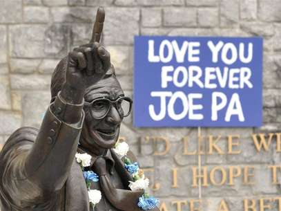 Signs and flowers are seen at the statue of the late Penn State football coach Joe Paterno, before the annual Spring football scrimmage in State College, Pennsylvania April 21, 2012. Foto: Pat Little / Reuters In English