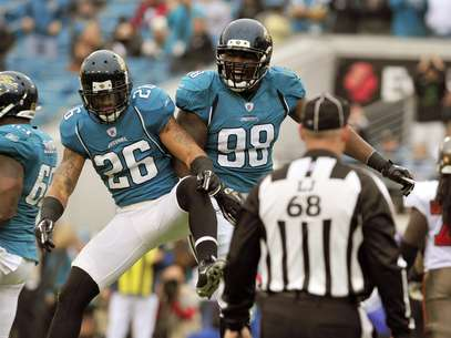 Former Jacksonville Jaguars defensive tackle Nate Collins (98) celebrates his fumble recovery for a touchdown with free safety Dawan Landry (26) during the first half of an NFL football game against the Tampa Bay Buccaneers on Sunday, Dec. 11, 2011, in Jacksonville, Fla. Foto: AP in English