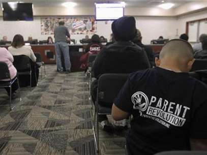 Eight-year-old Abraham Zamarripa sits in the audience in support of Patrick DeTemple, director of NGO Parent Revolution, who is speaking during a Adelanto School District board meeting regarding the parent trigger law, in Adelanto, California March 6, 2012. Foto: Alex Gallardo / Reuters In English