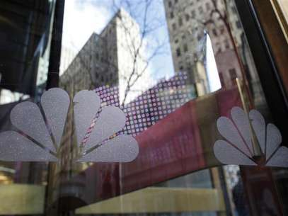 NBC logos are seen on a door with buildings around Rockefeller Center reflected in the background at the home of NBC's studios, in New York, December 3, 2009. Foto: Chip East / Reuters In English