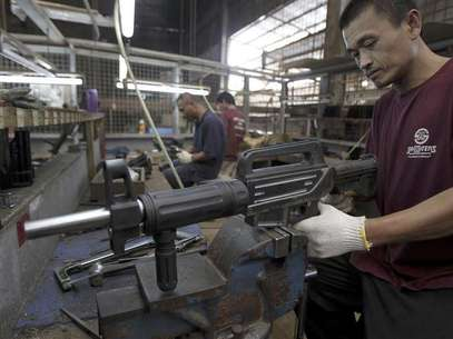 A former illegal gunsmith inspects a newly assembled multi-action shotgun at Shooters Arms, a gun manufacturing company exporting different kinds of weapons to other countries, in Cebu city in central Philippines July 7, 2012. Foto: Erik De Castro / Reuters In English