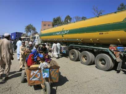 Men push a family past a fuel tanker, carrying supplies for NATO Forces, at the Pakistan-Afghan border of Torkham October 10, 2010. Foto: K. Parvez / Reuters In English