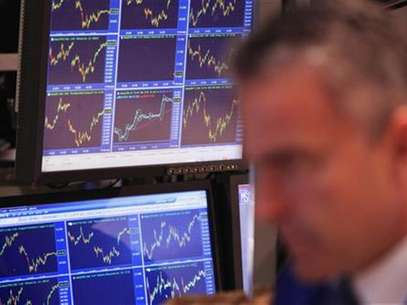 Price charts are displayed on a screen behind a trader as he works on the floor of the New York Stock Exchange after the closing bell in New York November 11, 2011. Foto: Lucas Jackson / Reuters In English