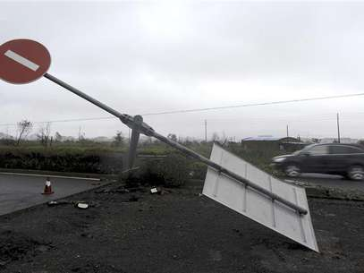 A car drives past a damaged traffic sign as Typhoon Haikui hits Hepu township, Zhejiang province, August 8, 2012. Foto: Lang Lang / Reuters In English