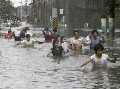 Residents wades through floodwaters on a submerged main street in Valenzuela, north of Manila August 8, 2012. Foto: Romeo Ranoco / Reuters In English