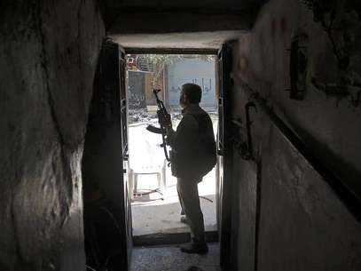 A Free Syrian Army fighter holds his gun as he looks at a street from a house during clashes with Syrian Army in the Salaheddine neighbourhood of central Aleppo August 7, 2012. Foto: Goran Tomasevic / Reuters In English