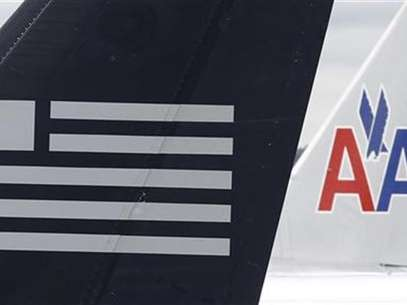 A US Airways plane and an American Airlines plane share a terminal at Ronald Reagan National Airport in Washington April 23, 2012. Foto: Kevin Lamarque / Reuters In English