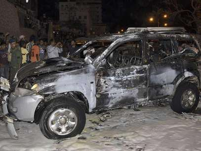 People look at the burnt car of Brigadier Omar Salim Ba-Rashid, the dean of the Military Academy, after a blast ripped through it in the southern Yemeni port city of Mukalla August 9, 2012. Foto: Stringer / Reuters In English