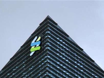 The logo of Standard Chartered is seen at its new Singapore office tower at the Marina Bay Financial Centre, January 24, 2011. Foto: Kevin Lam / Reuters In English