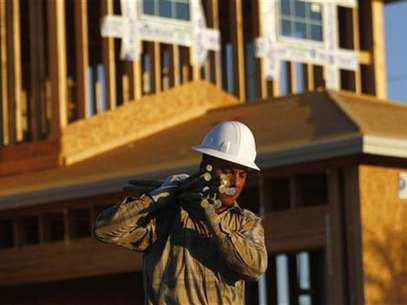 A worker carries materials for a house being constructed in Phoenix, Arizona, August 23, 2011. Foto: Joshua Lott / Reuters In English
