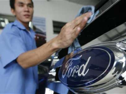 A worker waxes a car in a Ford automobile showroom in Manila June 28, 2012. . Foto: Cheryl Ravelo / Reuters In English